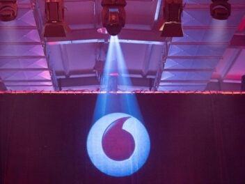 Das Vodafone-Logo wird an einer Wand von einem Lichtbeamer angestrahlt