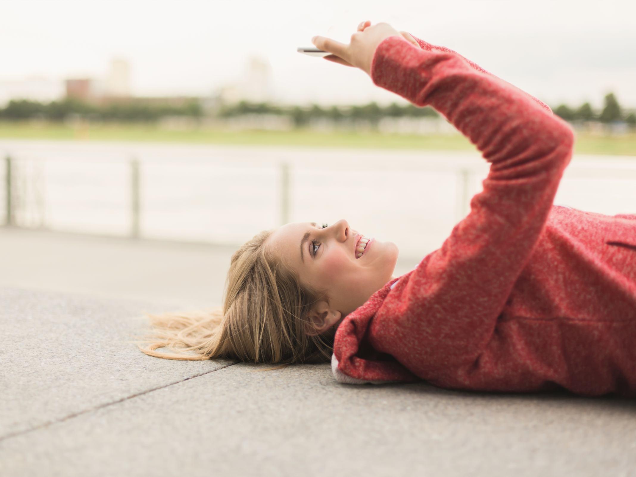 Eine Frau liegt entspannt auf dem Moden und nutzt ihr Handy