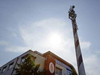 Ein Sendemast steht vor einem Gebäude mit Vodafone-Logo an der Wand