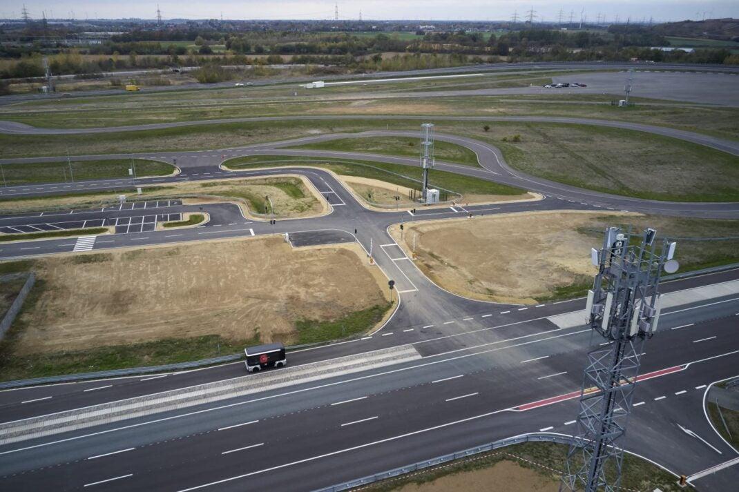Nlick auf das 5G-Testcenter Aldenhoven mit Sendemaste, einigen Straßen und Wegen und einem Kleinbus.
