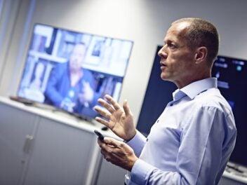 waipu.tv-Chef Christoph Bellmer. Im Hntergrund sind Fernseher zu sehen.