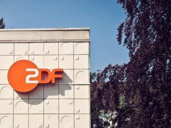 Das Logo des ZDF ist an einem Haus befestigt, rechts ist ein Baum zu sehen