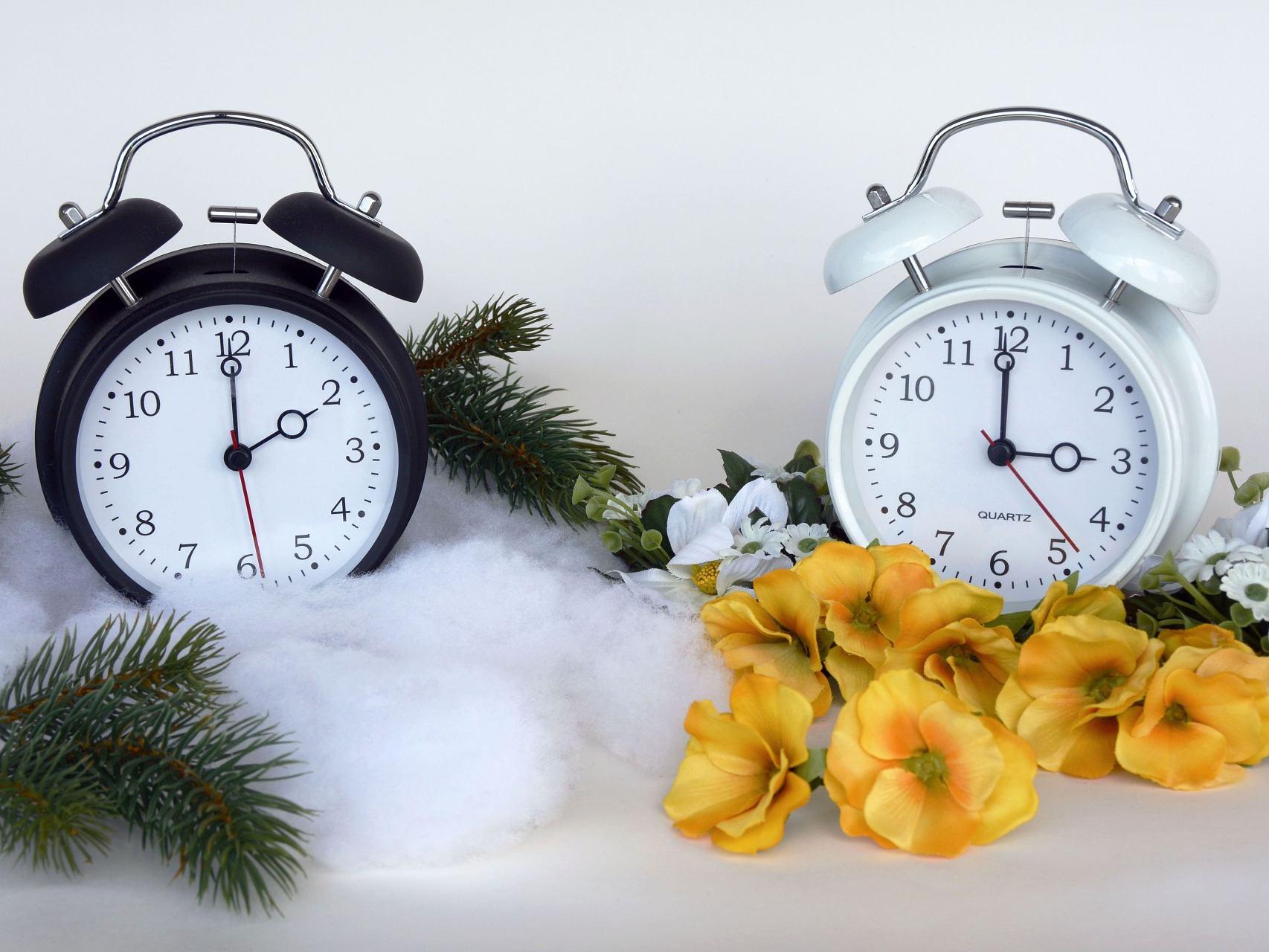 Zwei Wecker zeigen die Zeit 2 bzw. 3 Uhr an, davor liegt Herbst- und Frühjahrsdeko