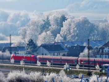 Ein Zug fährt an verschneiten Häusern vorbei